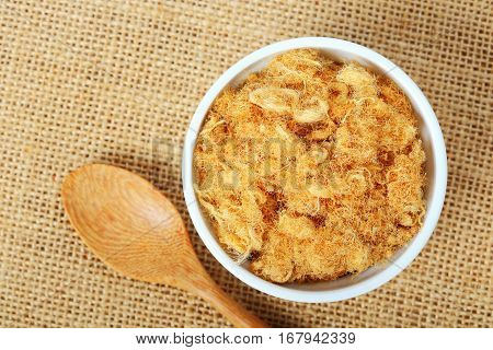 Top view of dried pork floss in white cup with wooden spoon on sack background.