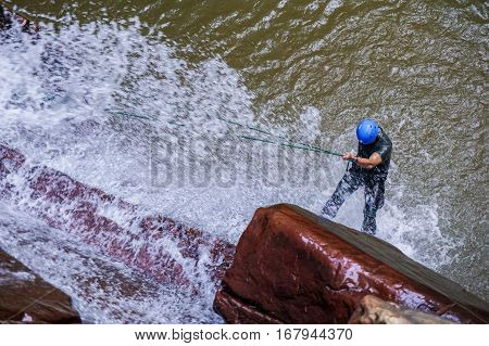 An adventurer man rapels with a rope over a waterfall in Beaufort,Sabah,Borneo.Waterfall Abseiling activity adventure getting famous in Sabah,Malaysia.