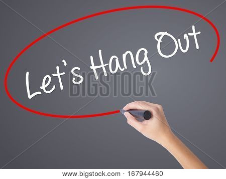Woman Hand Writing Let's Hang Out With Black Marker On Visual Screen