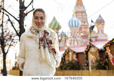 Portrait of a Young beautiful woman in white short mink coat, posing in winter Red Square in central Moscow