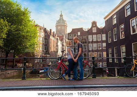Two lovers person in Amsterdam on a background of multi-colored house in the Dutch style stand and hold hands. Meeting of loving couple in the morning on the bridge over the canal near red bicycle.