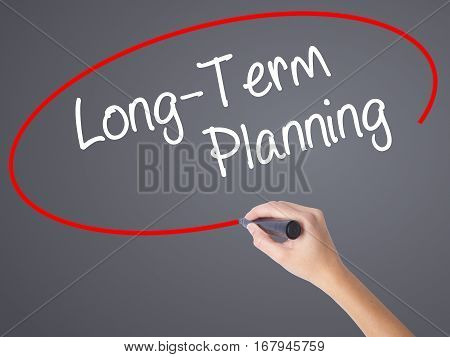 Woman Hand Writing  Long-term Planning With Black Marker On Visual Screen