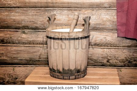 The interior of a small bath with wooden walls. On the bench a barrel made of oak planks for the water.