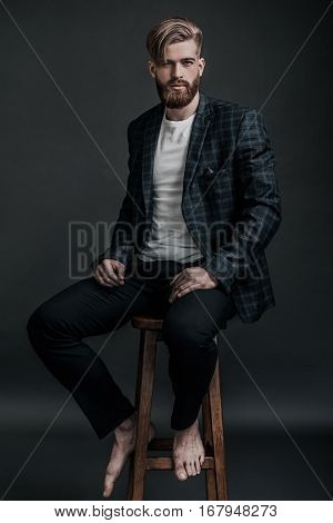 Handsome and bearded. Full length of attractive young man with long hair and beard looking at camera while sitting on chair against grey background
