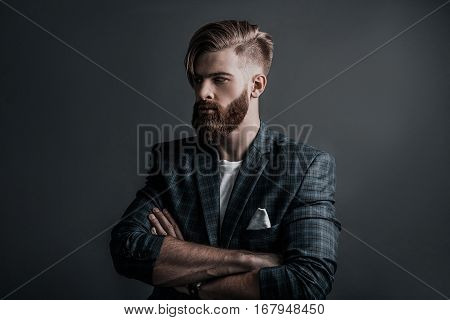 Confidence and charisma. Attractive young man keeping arms crossed and looking away while standing against grey background