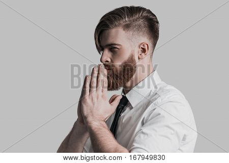 Lost in thoughts. Thoughtful young businessman holding hands clasped and looking away while standing against grey background