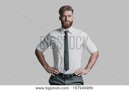 Young and successful. Handsome young man in formalwear keeping hands on hip and looking at camera while standing against grey background