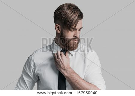 Thoughtful businessman. Young beautiful man adjusting his necktie and looking away while standing against grey background