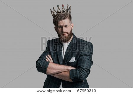 Prince of dreamland. Young hipster wearing crown and looking at camera while standing against grey background