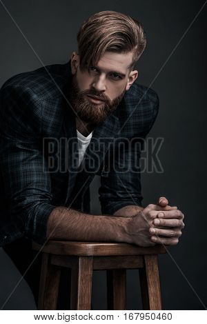 e looking in your heart. Confident man in casual clothing looking at camera while leaning on stool against grey background
