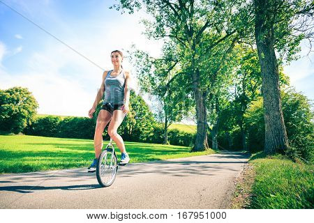 young athletic woman unicycling, having fun outdoors.