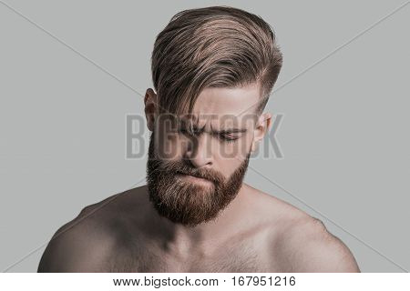 Upset about something. Portrait of young man keeping eyes closed while being in front of grey background