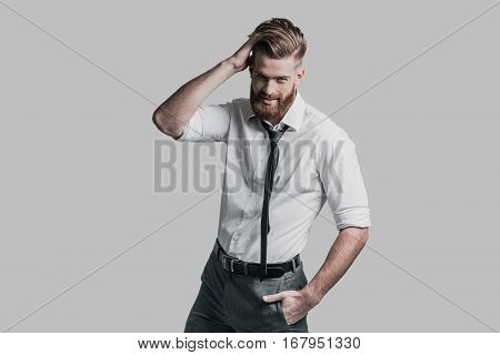Flirty handsome. Handsome businessman holding hand on head and looking at camera while standing against grey background