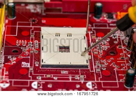 Computer technician is checking back side computer motherboard