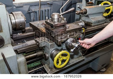 workmen working on industrial lathe close up