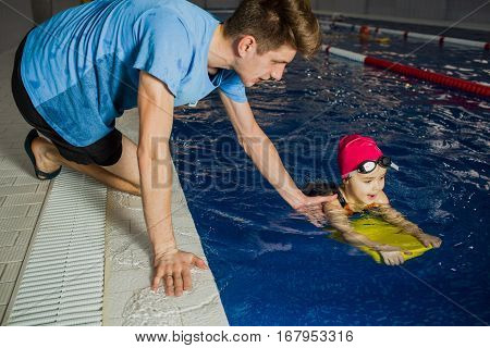 instructor teaches the child to swim in the pool