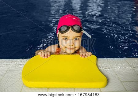 Portrait girl swimmer. child learns to swim in the pool