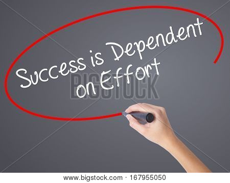 Woman Hand Writing Success Is Dependent On Effort With Black Marker On Visual Screen