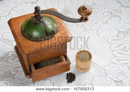 Peppercorns and ground pepper with a retro mill on the table.