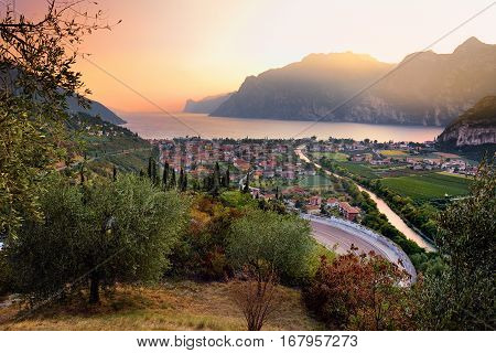 Scenic Aerial View Of Riva Del Garda Town, Located On A Shore Of Garda Lake, Surronded By Beautiful