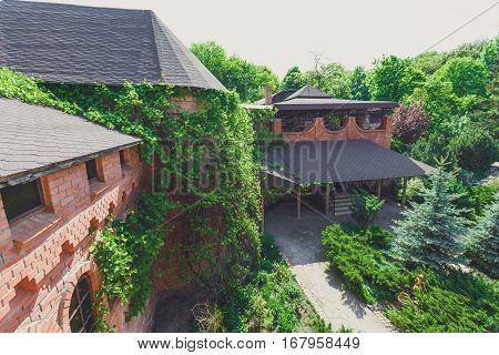Beautiful landscape design, garden path with stone tiles, evergreen bushes, fir trees, blue spruces and shrubs in sunlight. Modern landscaping near castle. Summer garden