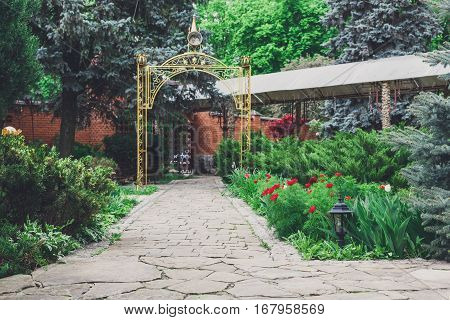 Beautiful landscape design, garden path to gazebo, evergreen bushes and shrubs in sunlight. Modern landscaping. Summer garden or park design.
