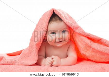 Newborn baby lying down and smiling in a terracotta color towel.