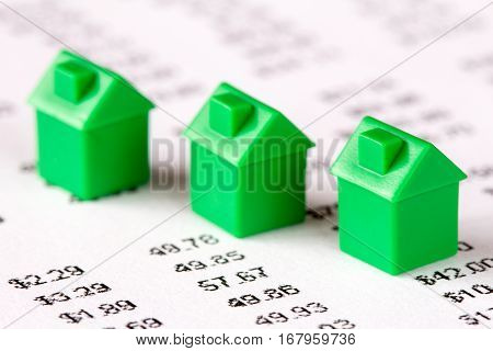 Green toy houses on a financial report background
