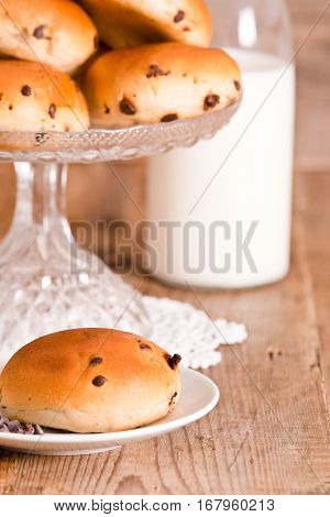 Chocolate chip brioche on white dish with bottle milk.