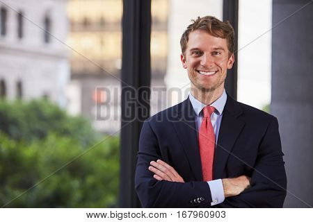 Young white businessman with arms crossed smiling, waist up