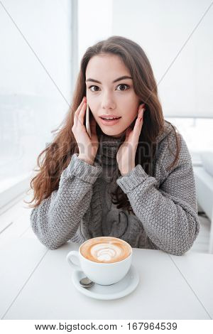 Picture of confused young lady dressed in sweater sitting in cafe at cold winter day and drinking coffee while talking by phone. Look at camera.
