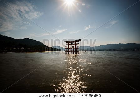 Wide angle backlit of Miyajima island with Floating Torii gate, Japan.