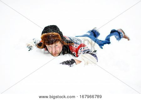 A man without a jacket lying in the snow