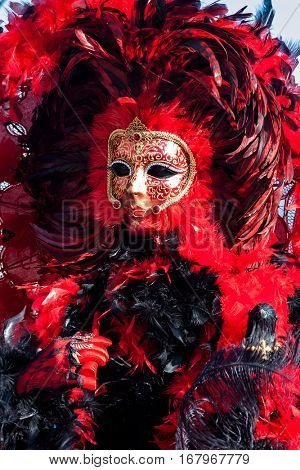 VENICE, ITALY - MARCH 04, 2011: Participant in colorful red costume and mask during traditional famous Carnival taking place each year on February in Venice.