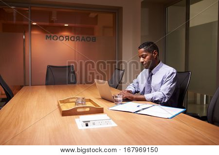 Middle aged black businessman working late alone in office