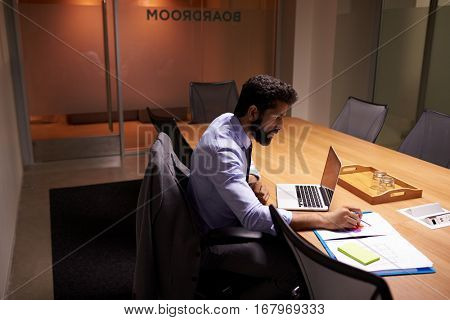 Hispanic businessman working late in office, elevated view