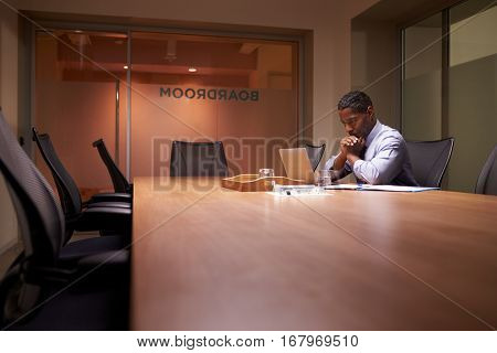 Middle aged black businessman works on laptop late in office