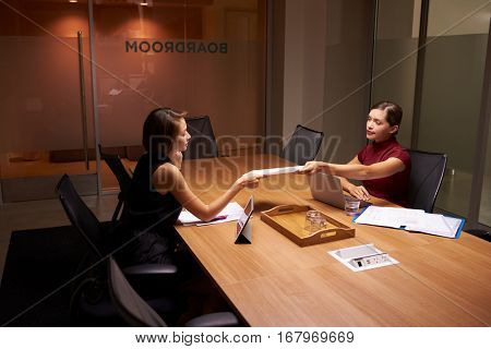 Two businesswomen working late in office passing documents