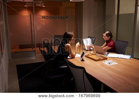 Two businesswomen working late in office look at documents