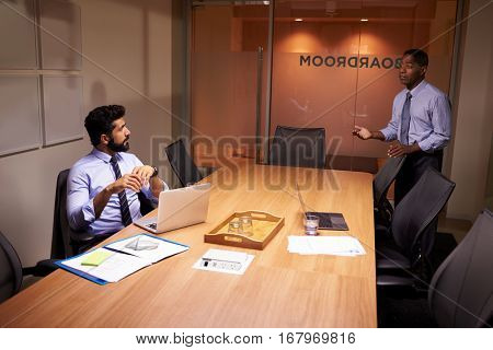 Businessman talks to colleague late in office, elevated view