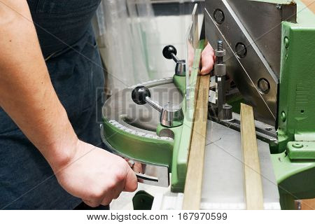 Craftsman working on frame in frameshop. Professional framer hand holding frame angle. Top view.