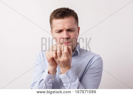 Young Man Stares At His Fingernails, Suffering From Fungus