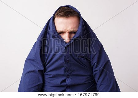 Young Man Hiding In A Blue Shirt, Knitting His Brows Angrily