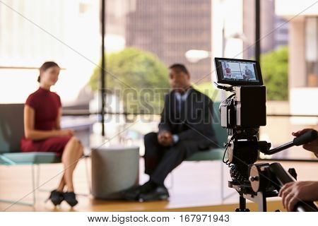 Black man and white woman on TV set, focus on foreground
