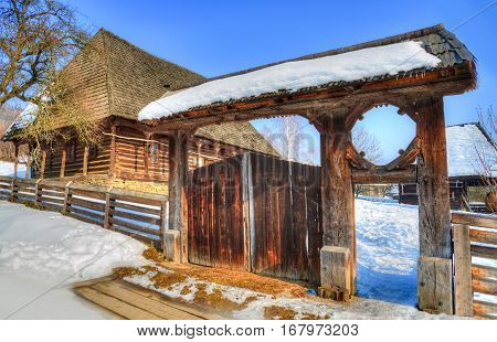 Traditional wooden house and gate of the village museum from Baia Mare, in winter season - Transylvania, Romania