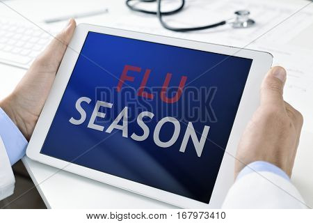 closeup of a young caucasian doctor man holding a tablet computer with the text flu season written in its screen
