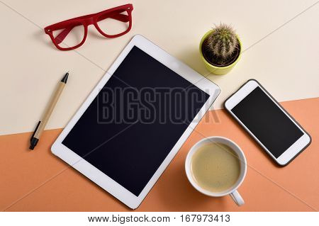 high-angle shot of an office desk full of things, such as a pair of red eyeglasses, a cup with white coffee, a tablet, a smartphone, a pen and a cactus