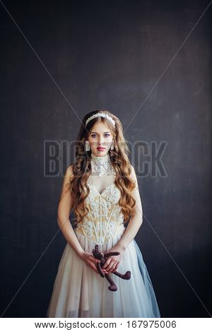 Fashion photo of young beautiful girl wearing wedding dress. Sad bride holding teddy bear. Professional make-up and hairstyle. Perfect skin. Fashion photo. Lolita style. Natural beauty.