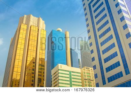 High rise modern buildings reflecting in the blue sky. Abu Dhabi, United Arab Emirates, Middle East. Finance and business concept. Urban city background.