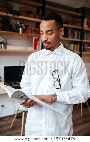 Picture of attractive african businessman standing in library and reading magazine. Look at magazine.